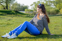 Woman Sitting Outdoors on Grass Near Lake. Young Woman Wearing Striped Shirt and Blue Jeans Reclining Outdoors on Grass Enjoying the Sunshine Near Lake Stock Images
