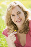 Woman sitting outdoors holding flower smiling. At camera Royalty Free Stock Photos