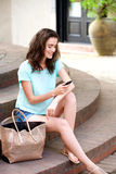 Woman  sitting outdoors with mobile phone Royalty Free Stock Images