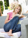 Woman sitting outdoors on patio with book smiling.  Royalty Free Stock Photography