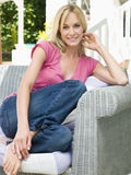 Woman sitting outdoors on patio smiling.  Royalty Free Stock Image