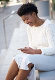 Woman sitting outdoors sending message on mobile phone Stock Image