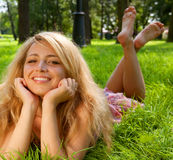 Woman sitting outdoors smiling Stock Images