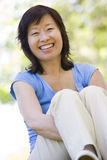 Woman sitting outdoors smiling. At camera Royalty Free Stock Photos
