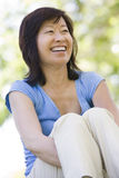 Woman sitting outdoors smiling. Looking away from the camera Royalty Free Stock Photos