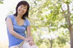 Woman sitting outdoors smiling. At camera Stock Photo