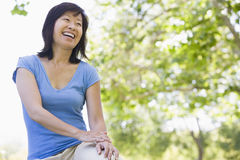 Woman sitting outdoors smiling. Away from camera Royalty Free Stock Photos