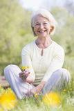 Woman sitting outdoors smiling. And holding a Buttercup flower Royalty Free Stock Photo