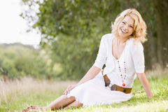 Woman sitting outdoors smiling. At camera Royalty Free Stock Photography