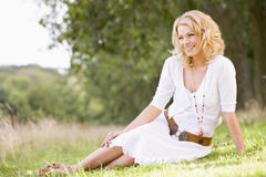 Woman sitting outdoors smiling. Away from camera Stock Photos