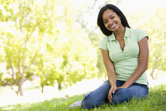 Woman sitting outdoors smiling. A Woman sitting outdoors smiling Royalty Free Stock Photo