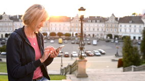 Woman sitting outdoors using smartphone. Closeup of a casual woman sitting outdoors using smartphone with city view at background. Sliding video stock video