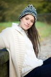 Woman sitting outdoors with white sweater and winter hat Royalty Free Stock Photo