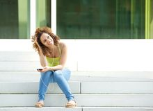 Woman sitting outside with earphones Royalty Free Stock Images