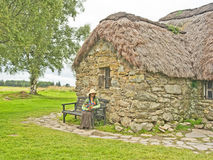 Woman sitting outside thatched cottage. Stock Photography