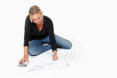 Woman sitting over a layout of a house stock photo