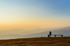 Woman sitting over the mountain top. Woman sitting on a bench over the mountain top Stock Photos