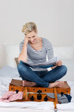 Woman Sitting On Overloaded Suitcase While Reading A Map Royalty Free Stock Images