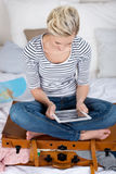 Woman Sitting On Overloaded Suitcase While Using Digital Tablet. Young woman sitting on overloaded suitcase while using digital tablet in bedroom stock images