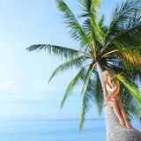 Woman sitting on palm Royalty Free Stock Image