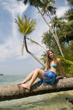 Woman sitting on palm tree Royalty Free Stock Image