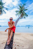 Woman sitting on palm tree Royalty Free Stock Photos