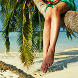 Woman sitting on a palm tree at tropical beach. Woman in green dress sitting on a palm tree at tropical beach, Maldives Royalty Free Stock Images