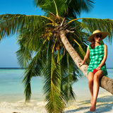 Woman sitting on a palm tree at tropical beach Royalty Free Stock Images