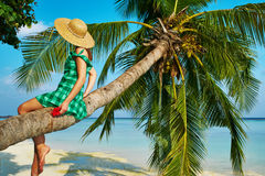 Woman sitting on a palm tree at tropical beach. Woman in green dress sitting on a palm tree at tropical beach, Maldives Stock Photography