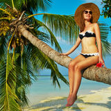 Woman sitting on a palm tree at tropical beach. Woman in bikini sitting on a palm tree at tropical beach, Maldives Royalty Free Stock Photography