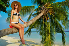 Woman sitting on a palm tree at tropical beach. Woman in bikini sitting on a palm tree at tropical beach, Maldives Stock Image