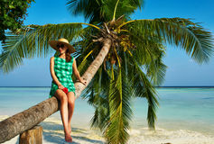 Woman sitting on a palm tree at tropical beach. Woman in green dress sitting on a palm tree at tropical beach, Maldives Stock Images