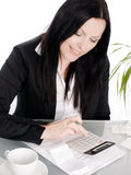 Woman sitting with papers and calculator Royalty Free Stock Photography