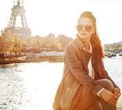 Woman sitting on the parapet and looking into distance in Paris Stock Photography