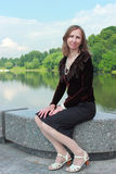 A woman is sitting on the parapet near the pond Stock Image