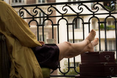 Woman sitting on Paris balcony with cup of coffee on her laps Royalty Free Stock Photo