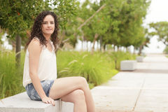 Woman sitting on a park bench Stock Photo