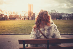 Woman sitting on a park bench Stock Photos