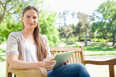 Woman sitting on a park bench with her tablet computer Royalty Free Stock Images