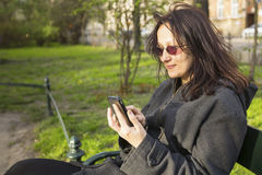 Woman sitting on a park bench speaks by phone. Stock Images
