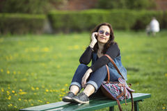 Woman sitting on a Park bench talking on a cell phone. Love. Stock Photography