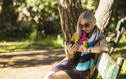 Woman sitting on a Park bench and typing on his smartphone. Stock Photos