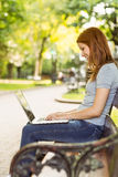 Woman sitting on park bench using laptop Stock Photography