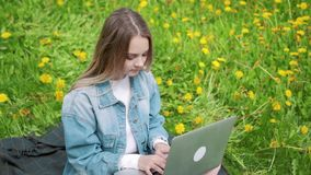 Woman sitting in park on the green grass with laptop, notebook. Student studying outdoors stock footage