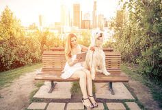 Woman sitting in a park with her dog. Watching the tablet and relaxing at sunset Stock Images