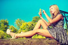 Woman sitting in park, relaxing and using phone Royalty Free Stock Images