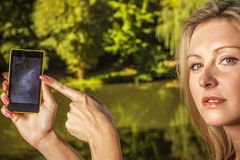 Woman sitting in park, relaxing and using phone Royalty Free Stock Photography