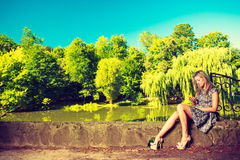 Woman sitting in park, relaxing and using phone Stock Image