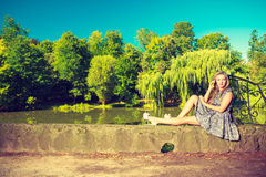 Woman sitting in park, relaxing and using phone Royalty Free Stock Photo
