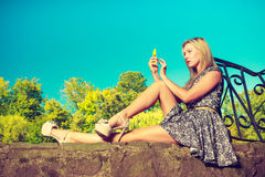 Woman sitting in park, relaxing and using phone Stock Photo